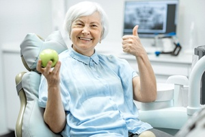 Smiling dental patient holding an apple