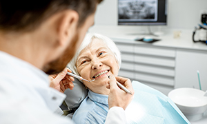 elderly woman smiling at dentist