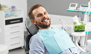 man in work clothes smiling at camera