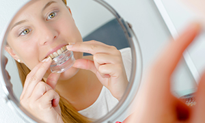 girl putting in clear mouthguard