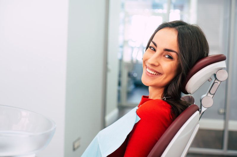 a young woman wearing a red blouse and smiling while waiting for her dentist to arrive