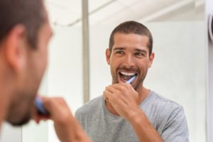 man looking in the mirror brushing his veneers