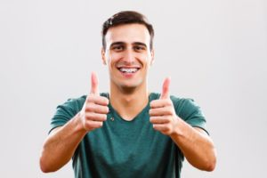 man with clean thumbs up thanks to his dentist
